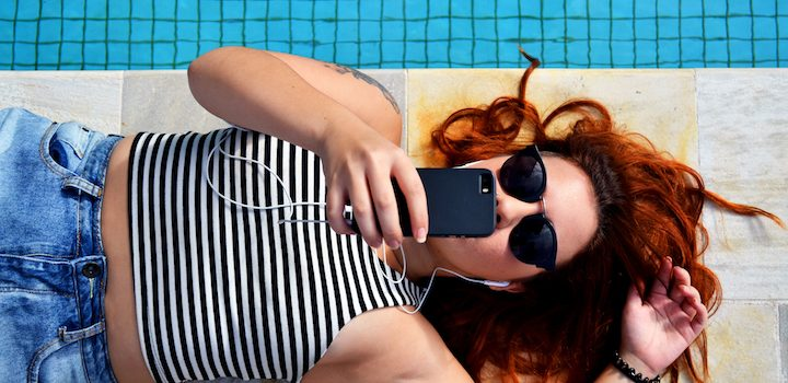 woman lying and listening to music on iphone