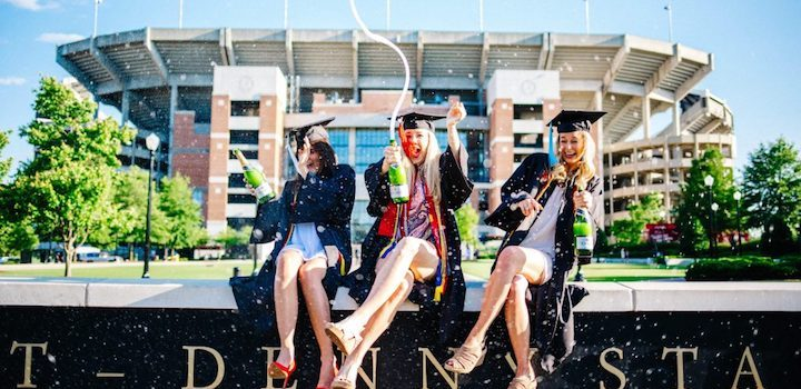 3 female students celebrating graduation from university and popping champagne
