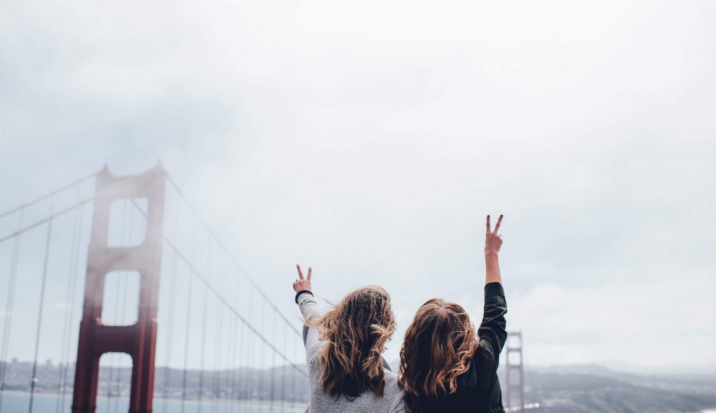 2 students making a photo of themselves in front of a big bridge in a foggy weather