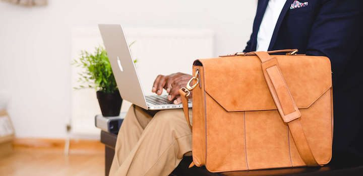 businessman with a macbook laptop and a leather bag