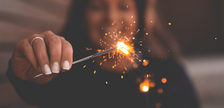 a woman holding a firework sparkler in her hand and celebrating a 2018 new year